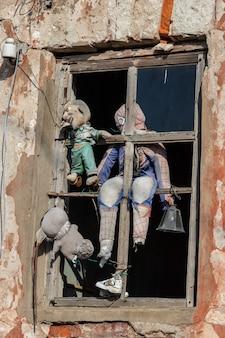 오래된 버려진 집의 주황색 벽에 있는 나무 창문에 있는 이상한 오래된 찢어진 인형