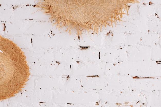 コピースペースと白いレンガの壁の背景に麦わら帽子。旅行のコンセプト。
