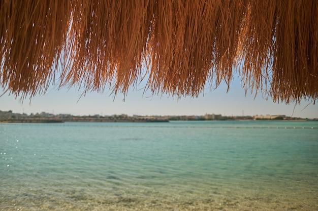 Соломенный зонт на красивом пляже