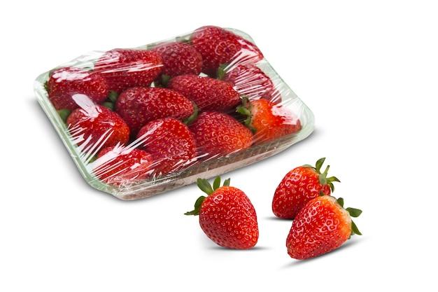 Клубника, разрезанная пополам, перед целыми тремя ягодами клубники. свежие фрукты
