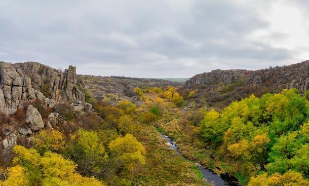 アクトフスキー峡谷とウクライナと秋の木々に小川が流れています