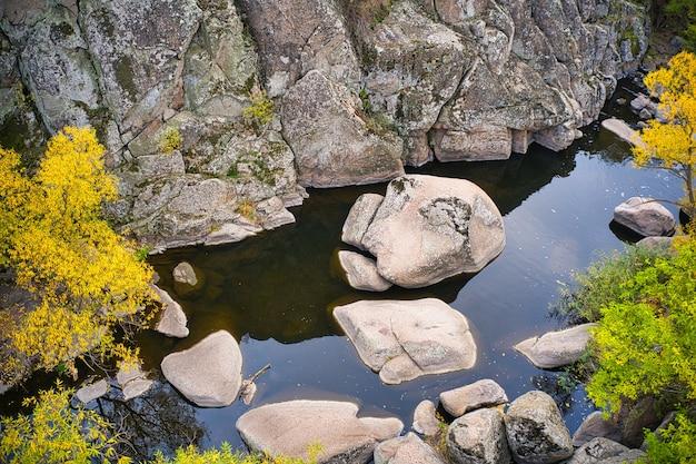 Ручей протекает в актовском каньоне, украина. осенние деревья и большие каменные валуны вокруг. панорамный снимок с дронов с воздуха