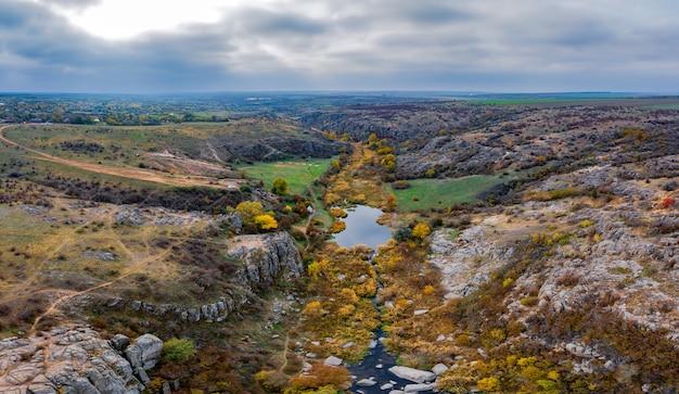 우크라이나 악 토프 스키 협곡에서 개울이 흐릅니다. 주변의 가을 나무와 큰 돌 바위.