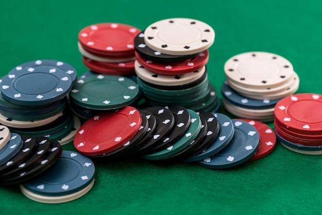 さまざまなカジノチップの流れが緑のテーブルにあります