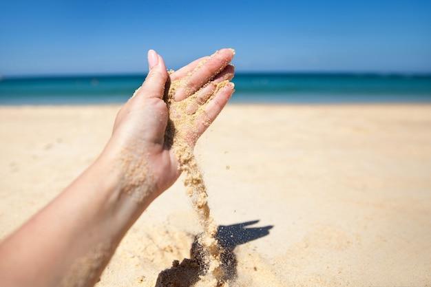 砂浜で女性の手から砂の流れが落ちる