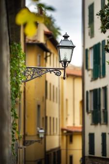 Уличный фонарь на узкой улочке во флоренции. тоскана, италия.