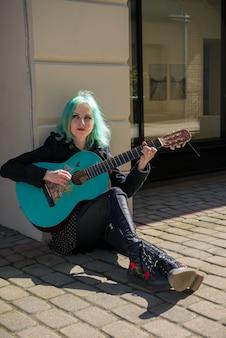 Уличный музыкант с синими волосами и синей гитарой сидит рядом со зданием.