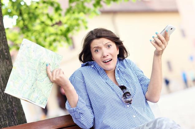 町で地図と携帯電話を持っているストレスのたまった女性