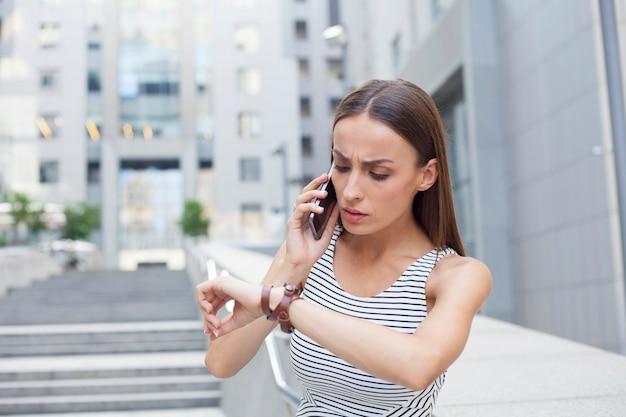 スマホを持ったストレスのたまった若い女性が時計を見ながら急いでいる。