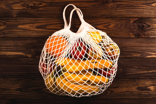 果物と野菜がいっぱい入ったストリングバッグ。エコライフスタイル。