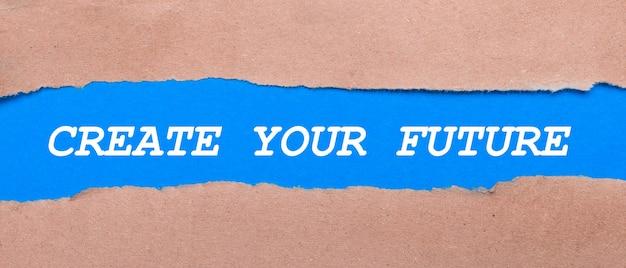 茶色の紙の間に「createyourfuture」と刻まれた青い紙のストリップ。上から見る