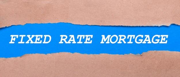茶色の紙の間にfixedratemortgageと刻まれた青い紙のストリップ。上から見る