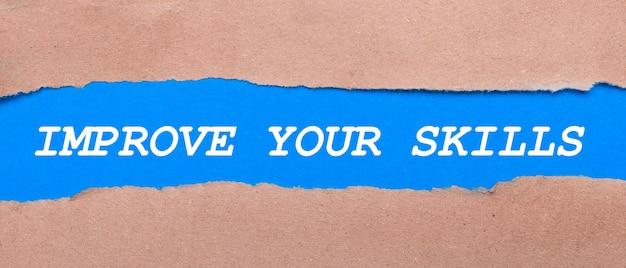 茶色の紙の間に「スキルを向上させる」と書かれた青い紙のストリップ。上から見る