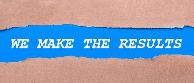 茶色の紙の間に「wemaketheresults」という言葉が書かれた青い紙のストリップ
