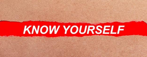破れた茶色の紙の下にある赤い紙のストリップ。赤い紙に白い文字があなた自身を知っています。上から見る