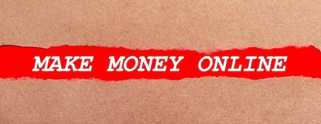 Полоска красной бумаги под рваной коричневой бумагой. белая надпись на красной бумаге зарабатывайте деньги онлайн. вид сверху