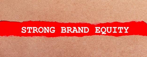 Полоска красной бумаги под рваной коричневой бумагой. белая надпись на красной бумаге strong brand equity. вид сверху