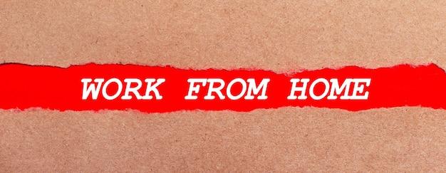 破れた茶色の紙の下にある赤い紙のストリップ。赤い紙に白いレタリングworkfromhome。上から見る