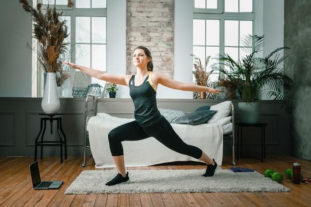 Сильная и красивая спортивная фитнес-девушка в спортивной одежде делает выпады с гантелями