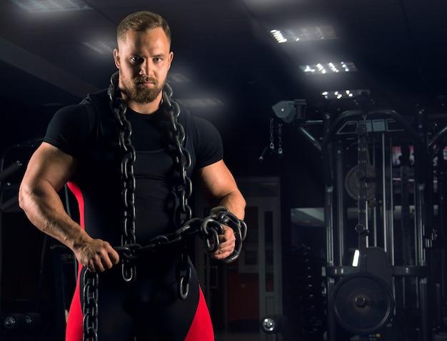 Сильный спортсмен носит жимовое оборудование с цепью на шее на фоне спортивных тренажеров.
