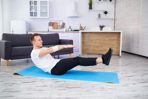 Сильный спортивный мужчина в футболке и дома делает упражнения на пресс в своей просторной и светлой квартире с минималистичным интерьером. занимаюсь спортом дома.