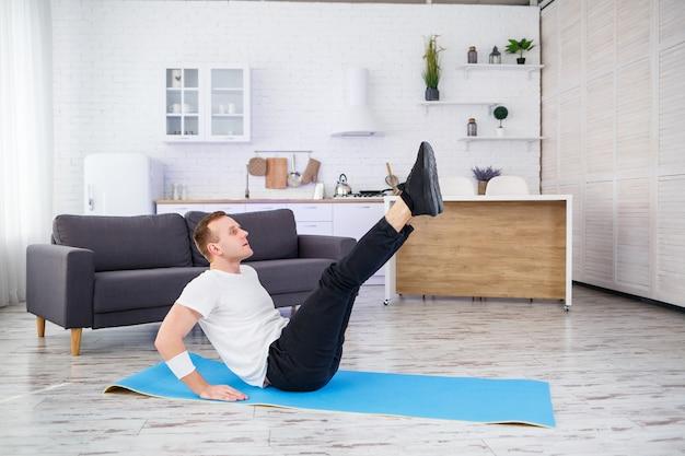 T셔츠를 입은 강한 운동선수와 미니멀한 인테리어가 있는 넓고 밝은 아파트에서 집에서 프레스 운동을 하고 있습니다. 집에서 스포츠를 합니다.