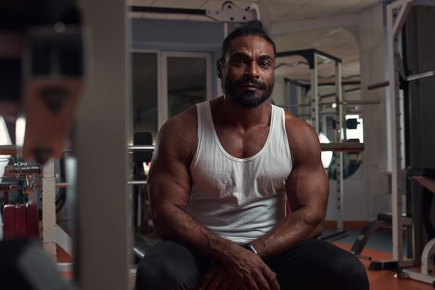 흰색 티셔츠와 검은색 운동복을 입은 강한 운동선수가 시뮬레이터 하이 q의 체육관에 앉아 있습니다.