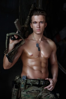 Сильный привлекательный солдат с мускулистым торсом в камуфляжной форме.