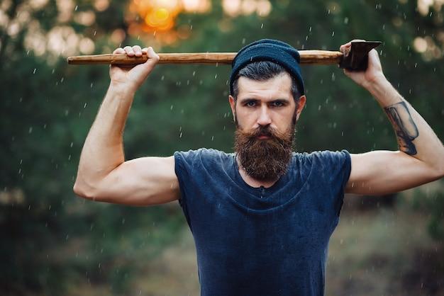 青いtシャツと暖かい帽子の長いひげと口ひげを持つ強いひげを生やした男木こりは斧を保持します