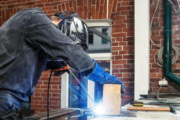 全体的に黒い構造の強い男性の溶接工と溶接綿棒が、金属構造の溶接機を木の棒に溶接します