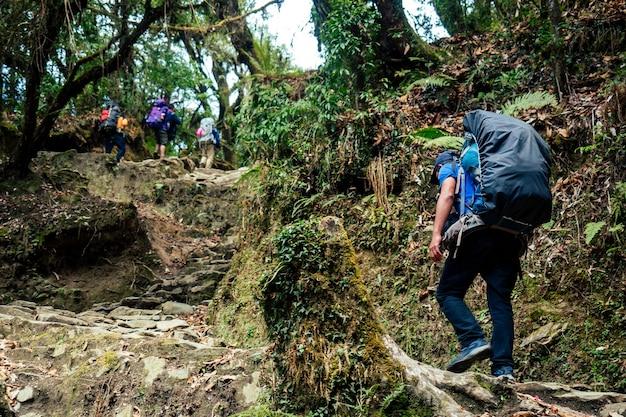 強い男が大きなバックパックを持って上り坂を登ります。ヒマラヤ山脈でのハイキングのコンセプト。