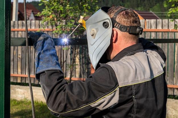 強い男は溶接マスクと溶接革の溶接工であり、金属製品が溶接されています
