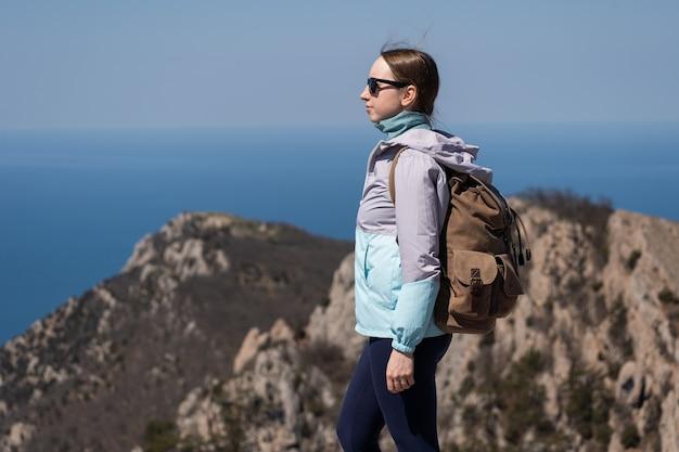 의지가 강한 젊은 여성이 산을 여행합니다. 의지력과 어려움 극복. 높은 곳에서 멋진 전망.