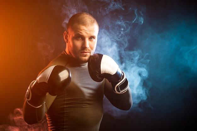 Сильный молодой темноволосый спортсмен-мужчина в зеленой спортивной куртке, в черно-белых боксерских перчатках боксирует на фоне синего и красного дыма на черном изолированном фоне
