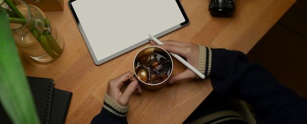 Студент держит кружку кофе со льдом во время выполнения задания