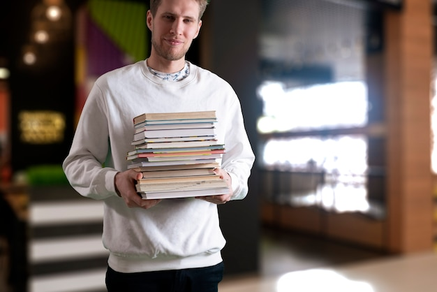 本のスタックを保持し、重い紙の教科書、動機付けの概念を運ぶ学生