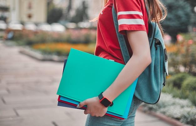그녀의 손에 배낭과 컬러 메모장이 있는 빨간 티셔츠를 입은 학생, 도시 광장의 백플레인