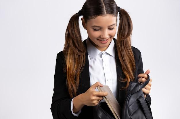 학생은 배낭에 책을 넣습니다 웃는 소녀 실내 흰색 벽 포즈