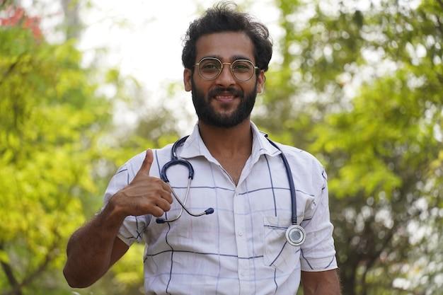聴診器を持って親指を立てる学生と成功の兆候を示す学生-医学教育の概念