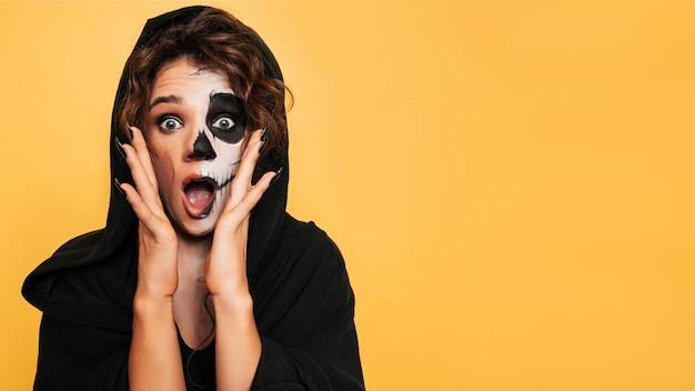 Студийный снимок девушки, выражающей испуг в костюме злых духов на костюмированной вечеринке на хэллоуин. пустое место для товаров, рекламы. искусство хэллоуина.