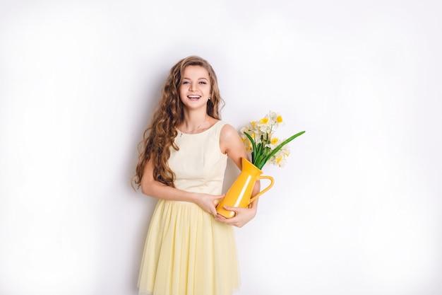Студийный снимок девушки, стоящей и держащей желтую вазу с цветами. у девушки длинные вьющиеся светлые волосы и уныло-желтое платье. девушка широко улыбается