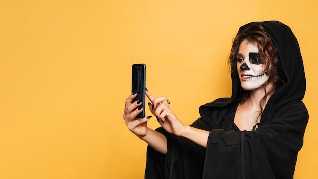 Студийный снимок девушки, делающей селфи в костюме злых духов на костюмированной вечеринке на хэллоуин. пустое место для товаров, рекламы. искусство хэллоуина