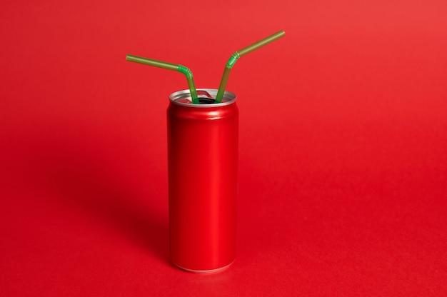 Студийный снимок с мягкой тенью красной металлической банки с кольцом и двумя зелеными соломинками на красном фоне. зелено-красный, цветовой контраст