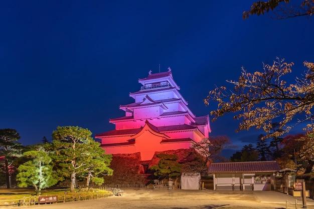 Потрясающая ночная сцена полного цветения гинкго в замке цуруга-дзё, освещенная ночью. айдзу вакамацу, фукусима, япония.