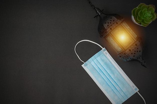 검은 배경에 멋진 라마단 촛불 랜턴과 의료용 얼굴 마스크