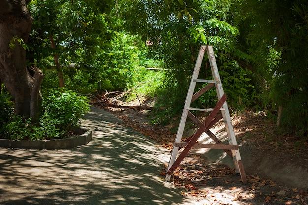 コピースペースのテキスト、木で修復されたアルミニウム階段のある庭のスタイルのはしご