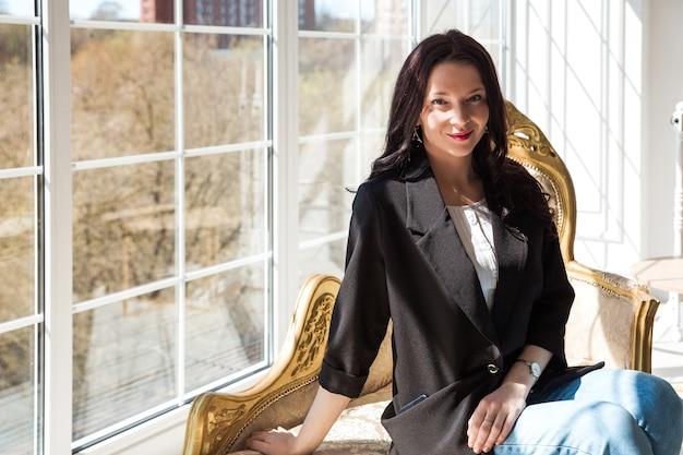 Стильная и красивая женщина в черной куртке сидит на золотом диване, улыбается и смотрит в камеру.