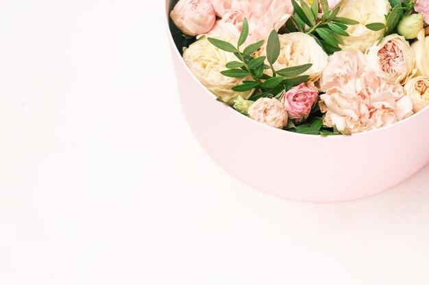 Стильная и нежная цветочная композиция в шляпной круглой коробке на розовом фоне с копией пространства