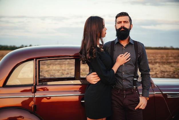 シャツとサスペンダー付きのズボンを着たスタイリッシュなひげを生やしたブルネットは、フィールドの背景にある茶色のレトロな車の近くにある黒いショート ドレスを着た長い髪の細い若い女の子を抱きしめます