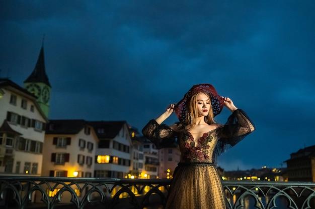취리히 구시 가지에서 밤에 검은 웨딩 드레스와 빨간 모자를 입은 세련된 신부가 포즈를 취하고 있습니다. 스위스.